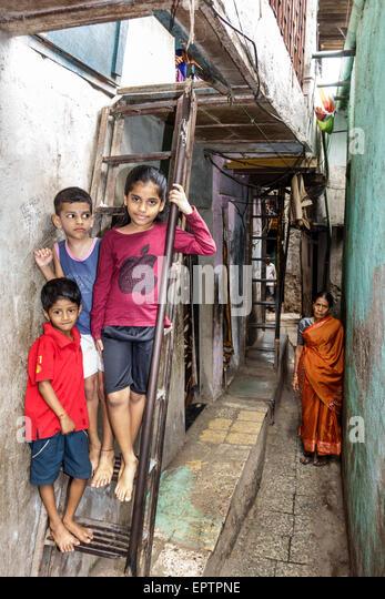 Mumbai India Asian Dharavi Kumbhar Wada slum high population density poverty low income poor resident boy girl friends - Stock Image
