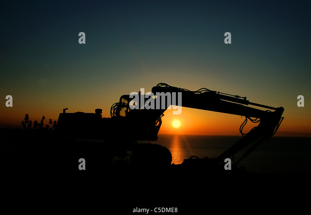 Silhouette  of a digger - Stock Image