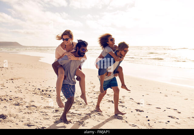 Two beautiful young couples walking along the beach, with men giving piggyback ride to women. Piggyback games on - Stock Image
