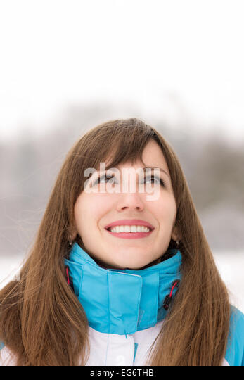 Young caucasian woman looking on copy space in outdoor snowy cold winter day. - Stock Image