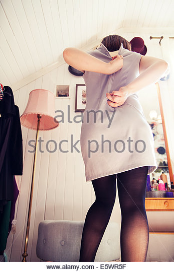 Rear view of young woman struggling to zip up dress - Stock Image