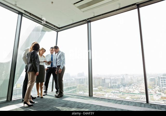 Businesspeople in office with woman using digital tablet - Stock Image