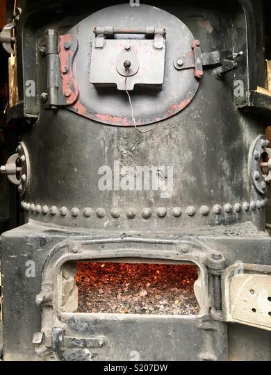 Old boiler with furnace door open - Stock Image