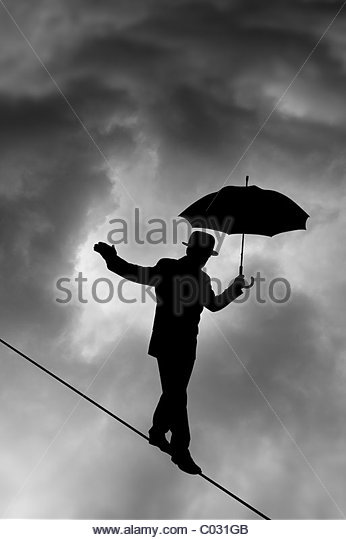 Tightrope Silhouette against black cloud - Stock Image
