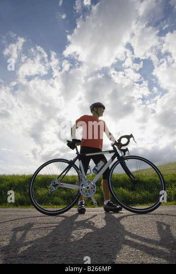Front view of a man standing on road with bicycle - Stock Image