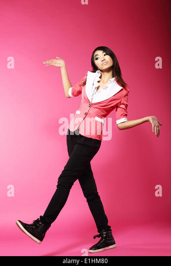 Asian Amusing Teenager Walking in Pink Studio - Stock Image