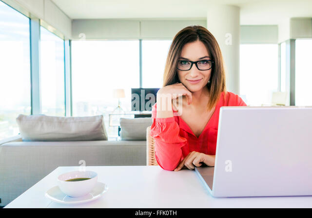 Woman in apartment using laptop computer - Stock-Bilder