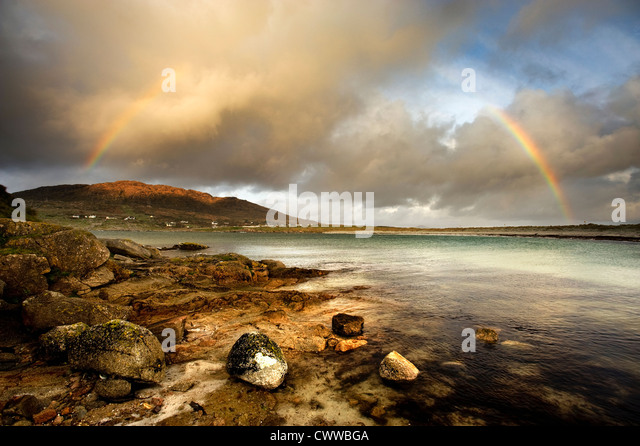 Rainbow stretching over still rural lake - Stock Image