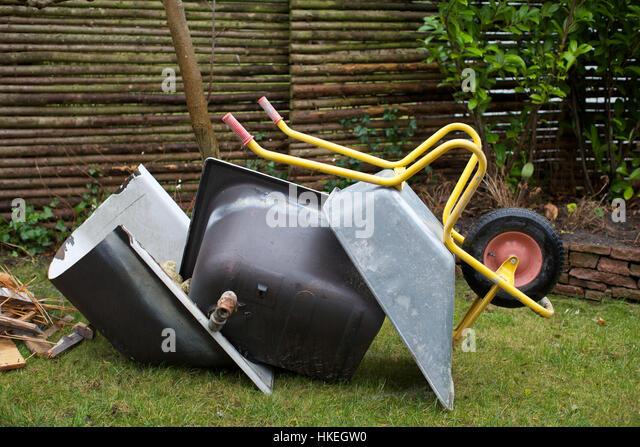 fallen wheelbarrow at garden. lawn, garden cart, grass, upside down. - Stock Image