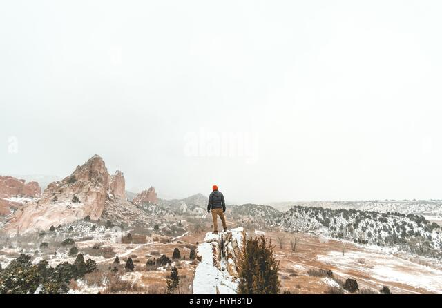 Man looking over expansive snow capped view in Garden of the Gods in Colorado, USA. - Stock Image