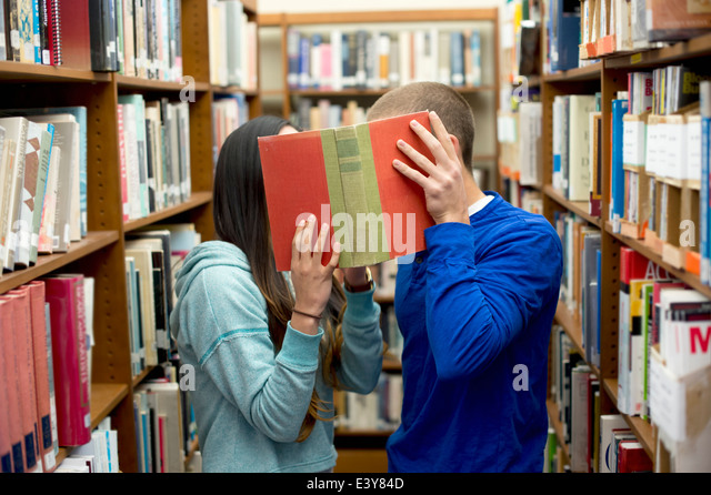 Young couple hiding behind book - Stock Image