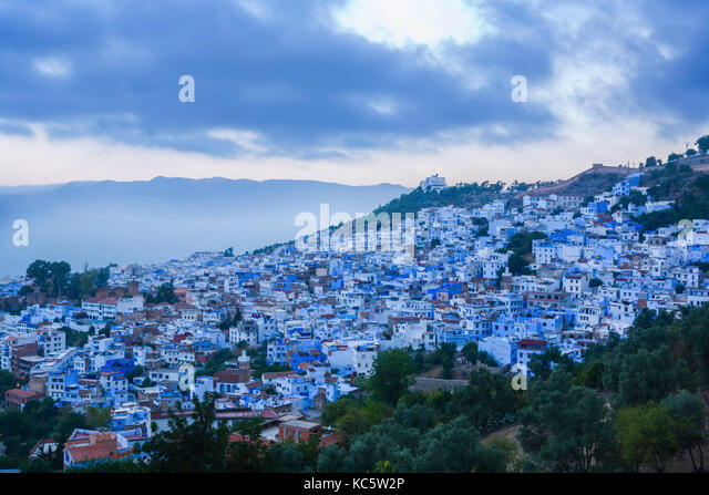 Panoramic view of blue city of Chefchaouen at rising, Morocco. Clouds over summits - Stock Image