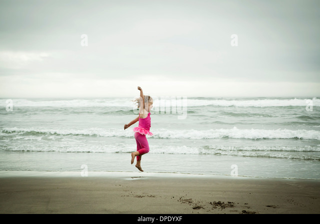 Female toddler jumping on beach - Stock Image