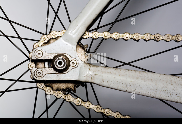 Close up of the rear wheel, cogs, spokes and chain of a single speed racing bicycle - Stock Image