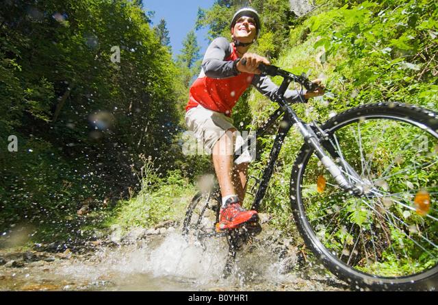 Mountainiker crossing brook - Stock Image