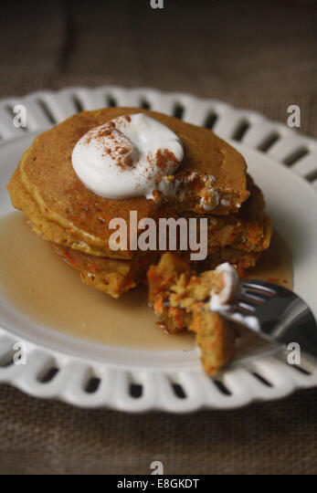 Carrot cake pancakes with yogurt, warm maple syrup and cinnamon - Stock Image