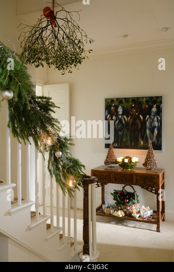 Festive decorated entrance hall with mistletoe, candlelit console table and pine garland - Stock Image