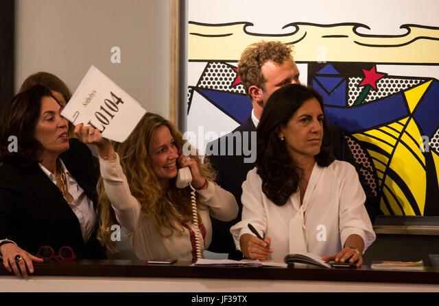 London, UK. 28 June 2017. Sotheby's staff taking telephone bids from cliients in front of Roy Lichtenstein's - Stock-Bilder