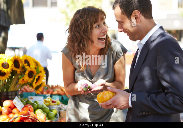 Smiling Couple at Farmers Market Holding Vegetables - Stock Image