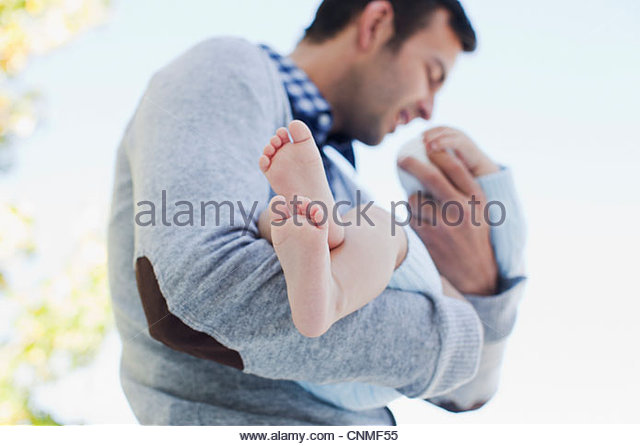 Father holding baby outdoors - Stock-Bilder