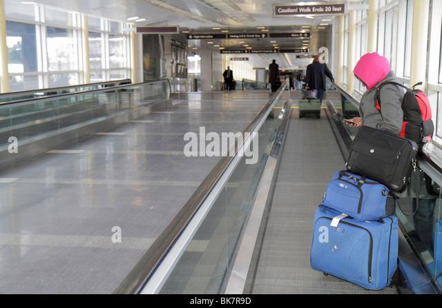 Washington DC Ronald Reagan Washington National Airport DCA terminal moving sidewalk Black woman using PDA wireless - Stock Image