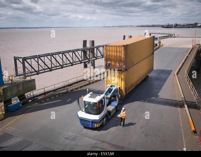 Elevated view of truck and shipping container on ramp to ship - Stock-Bilder