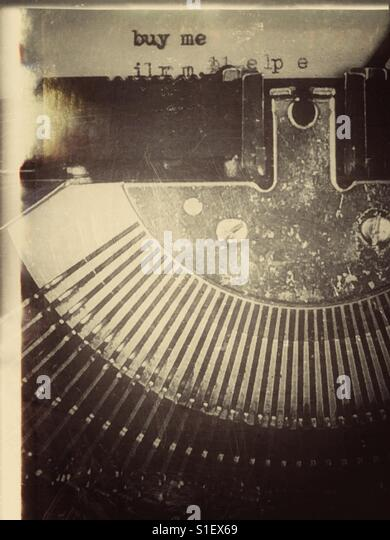Distressed and aged photo of typewriter with words 'buy me' typed out - Stock Image