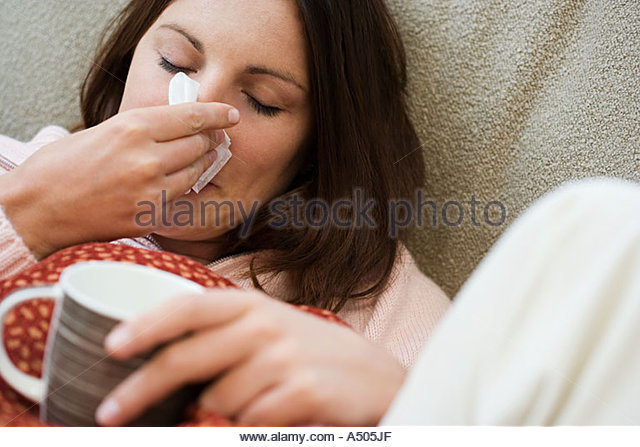 Woman with tissue and hot drink - Stock-Bilder