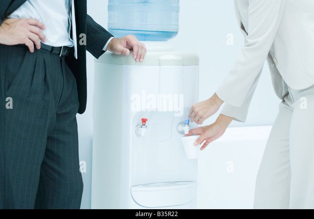Professional woman filling disposable cup with water from water cooler, male colleague standing nearby, cropped - Stock-Bilder