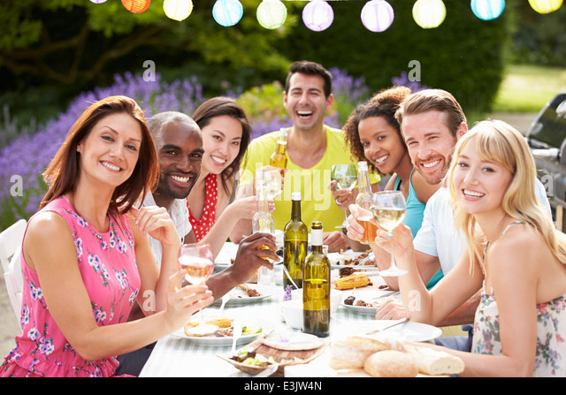 Group Of Friends Having Outdoor Barbeque At Home - Stock Image