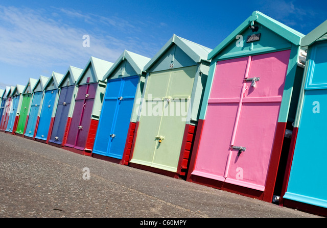 East Sussex , Hove actually , colorful or colourful beach huts on the promenade or seafront - Stock Image