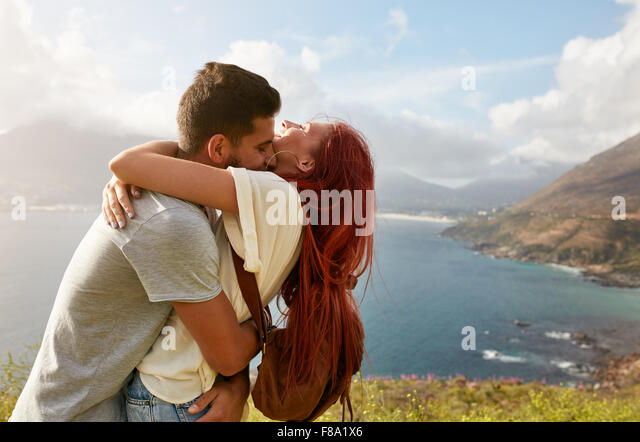 Loving young couple embracing and kissing on a summer day outdoors. Man hugging his girlfriend. Enjoying their summer - Stock-Bilder