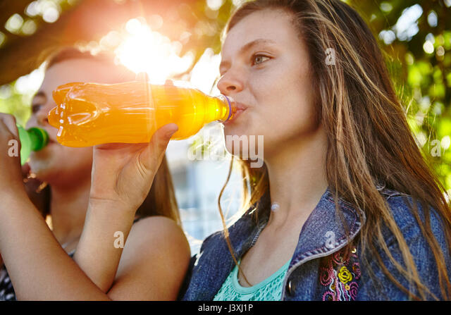 Two female friends sitting outdoors, drinking soft drinks - Stock Image