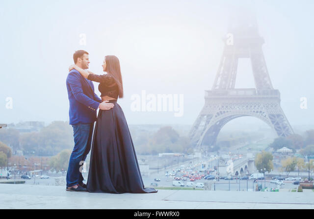 happy couple traveling in Paris, smiling man and woman posing in fancy fashion clothes on Eiffel Tower background - Stock Image