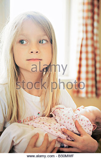 Close up of a girl carrying her sister - Stock Image