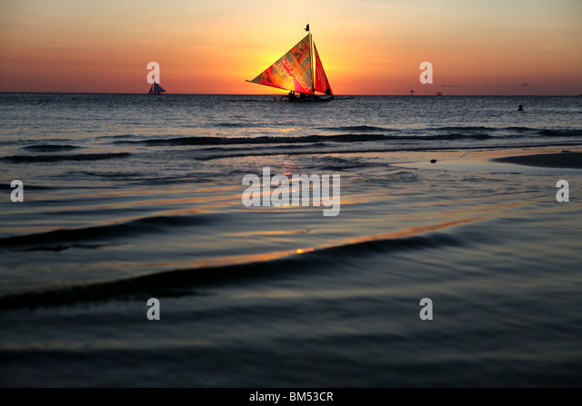 A sail boat passes the sunset on White Beach, Boracay, the most famous tourist destination in the Philippines. - Stock-Bilder