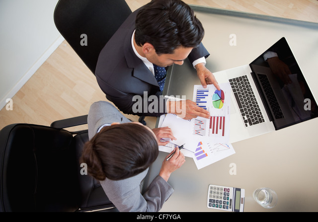 Sales persons studying statistics - Stock Image