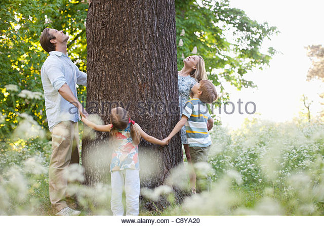 Family standing in circle around tree - Stock Image