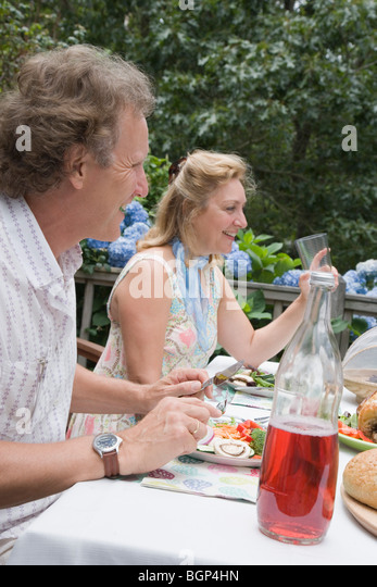 Mature couple having breakfast and smiling - Stock-Bilder