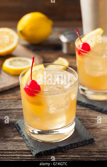 Homemade Whiskey Sour Cocktail Drink with a Cherry Lemon - Stock Image