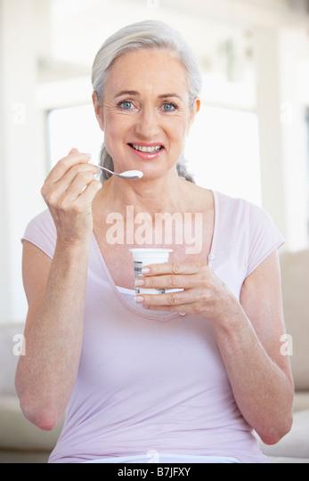 Senior Woman Eating Yogurt - Stock Image