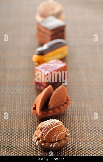 Row of chocolate Petit fours - Stock Image