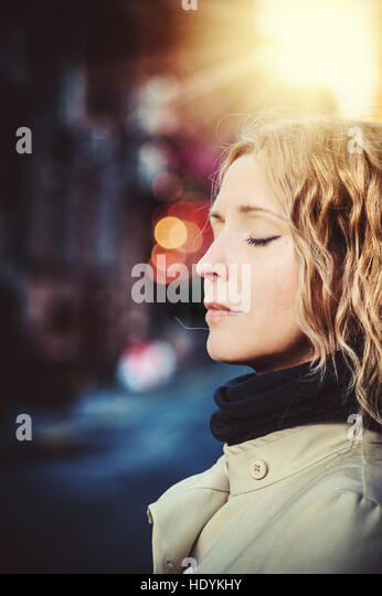 young woman with closed eyes in city - Stock Image