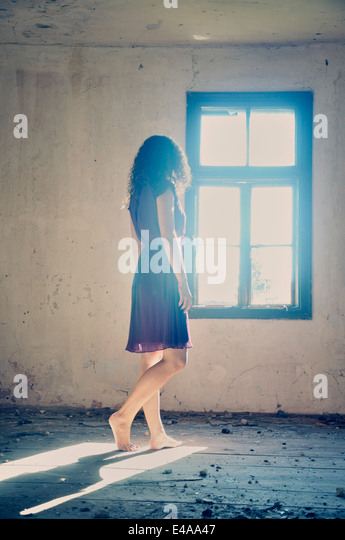 Young woman standing by the window - Stock-Bilder