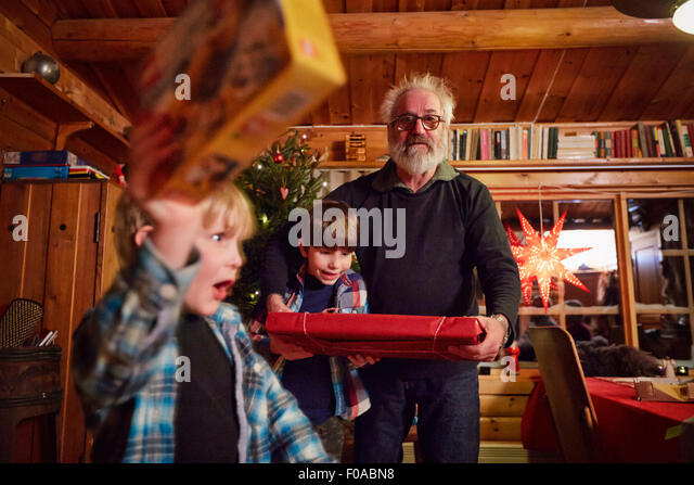 Joyful boy holding up Christmas present - Stock Image