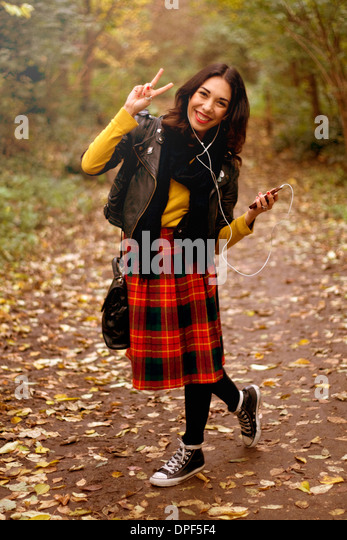 Young woman in park, listening to music using earphones, making peace sign - Stock-Bilder