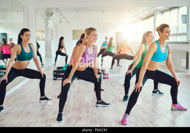 fitness, sport, training, people and lifestyle concept - group of women making squats in gym - Stock Image