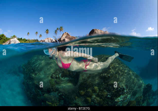 Snorkeling in Baths beach, British Virgin Islands, female diver, oval mask, bikini, blue water, clear water, snorkel, - Stock Image