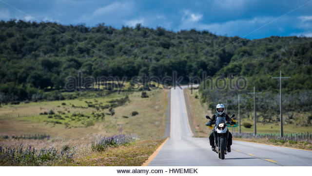 Woman driving her motorbike on lonely road in Patagonia, Chile - Stock-Bilder