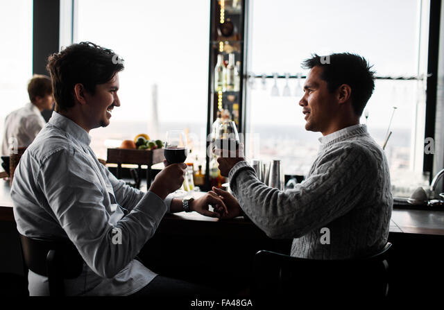 Gay couple toasting with red wine at table in Sky bar restaurant - Stock Image